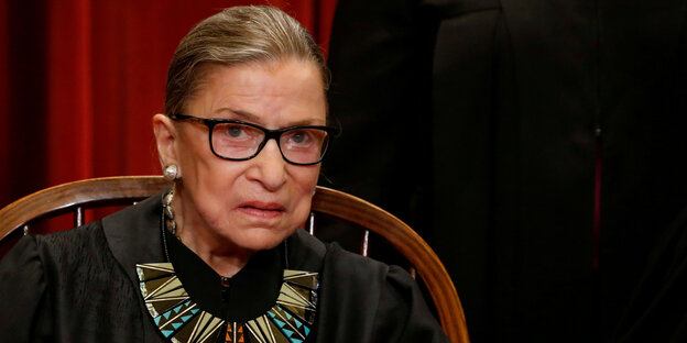 Ruth Bader Ginsburg sits on a chair with a serious look