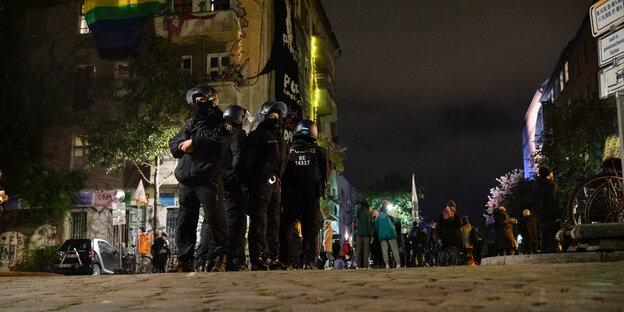 Polizist:innen stehen behelmt und Rücken an Rücken auf einer Kreuzung. Im Hintergrund ist ein Haus mit viel Graffitis zu sehen.