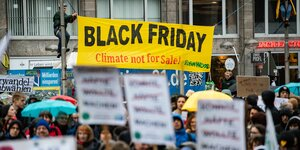 "Demonstration mit gelbem Banner mit der Aufschrift ""Black Friday Climate not for sale"""