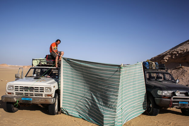 Zwei Autos in der Wüste, zwischen ihnen ist ein Windschutz aufgespannt, Ein Mann steht auf dem Dach des einen Autos