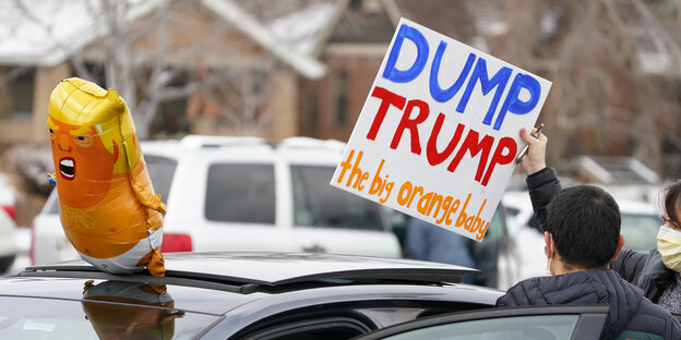 "gelber Trump Ballon und Schild ""Dump trump the big yellow baby"""