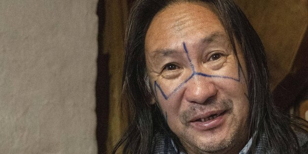 Mann mit langen Haaren und bemaltem Gesicht