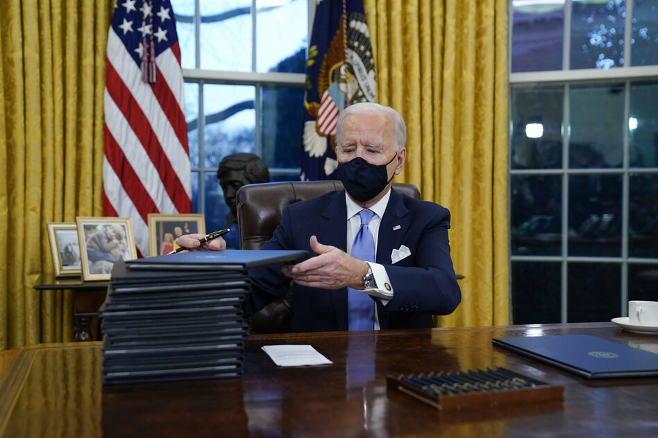 Joe Biden in the Oval Office with mouth and nose protection grabs files from a pile on the desk