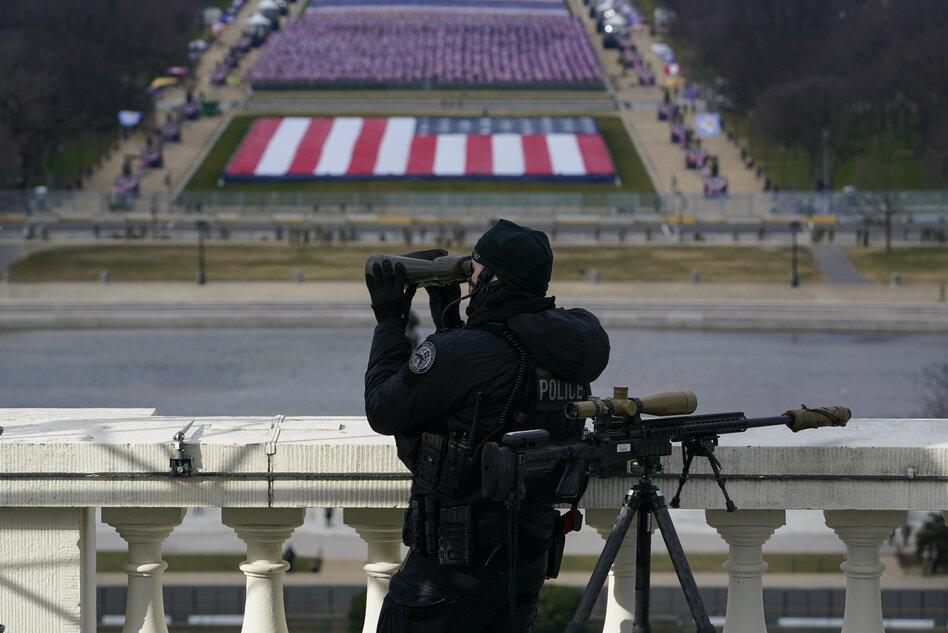 A sniper on a roof looks through binoculars