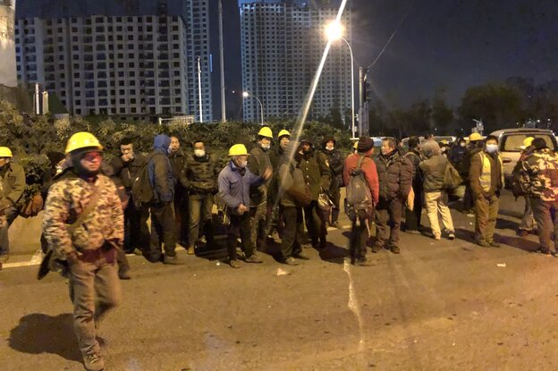 Workers with yellow helmets and protective masks stand waiting in front of the high-rise building