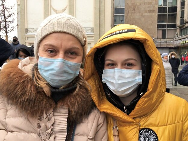 Two women with face masks stand close together