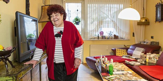 Eine ältere Frau lacht in ihrem Wohnzimmer in die Kamera