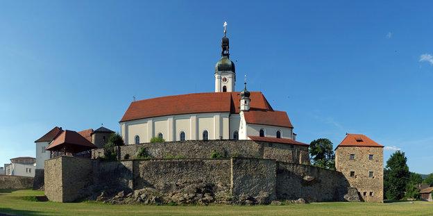Hübsche kirche mit mittelalterlicher stadtmauer vor strahlend blauem himmel
