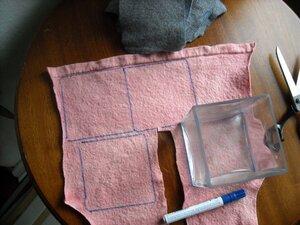 Ein Stück rosa Filz, auf dem Quadrate eingezeichnet sind und eine Schere zum Ausschneiden liegt bereit