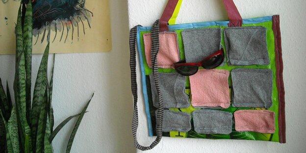 Eine Tasche, verziert mit Filzquadraten, hängt an einer Wand