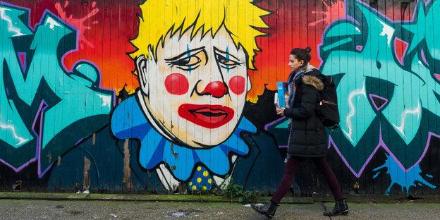 A woman walks past a graffiti depicting Boris Johnson as a clown