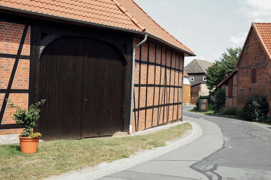 Eine Dorfstraße, im Vordergrund eine Fachwerkscheune