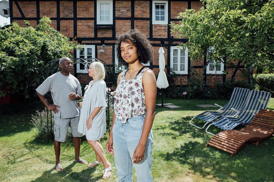 Im Vordergrund eine junge Schwarze Frau; im Hintergrund eine weiße Frau und ein Schwarzer Mann