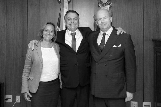 Ein schwarz-weiß Foto von Beatrix von Storch und ihrem Mann, die von Jair Bolsonaro umarmt werden. Alle lachen in die Kamera