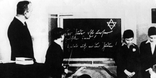 Eine Schulklasse zur NS-Zeit. Ein Schüler steht vor einer Tafel, auf der ein Davidstern zu sehen ist.