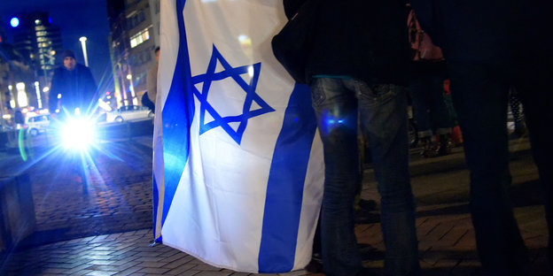 Jemand hält eine Flagge, auf der ein Davidstern zu sehen ist.