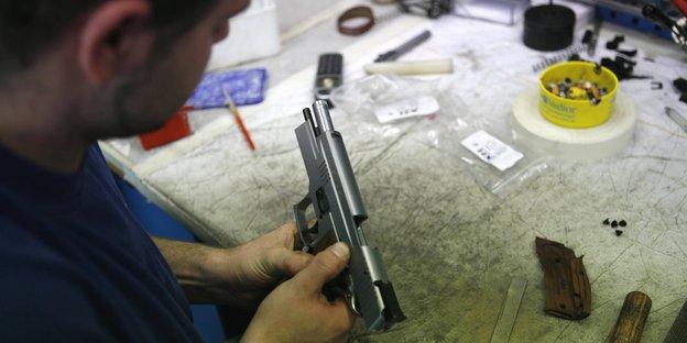 Bei einem Waffenhersteller. Ein Mann setzt eine Pistole zusammen.