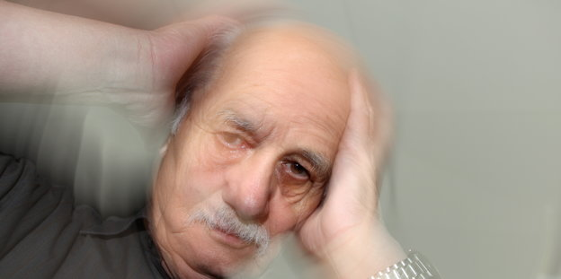 Ein Mann hält die Hände an den Kopf