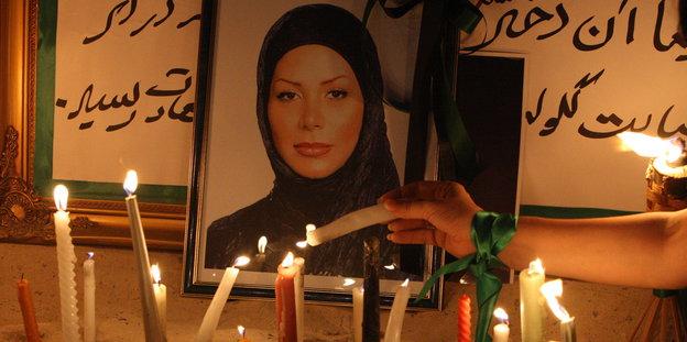 Eine Frau mit einem grünen Band um das Handgelenk macht eine Kerze bei einem Gedenkaltar an