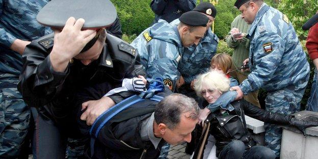 Polizisten halten Menschen gewaltsam fest, sie hocken auf dem Boden