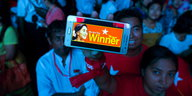 "Ein blau angeleuchteter Mensch hebt ein Smartphone mit der Display ""We are the winner"" hoch"