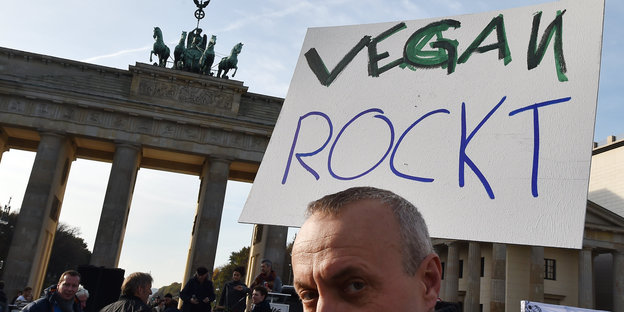 "Demonstrant mit Transparent ""vegan rockt"" vor dem Brandenburger Tor"