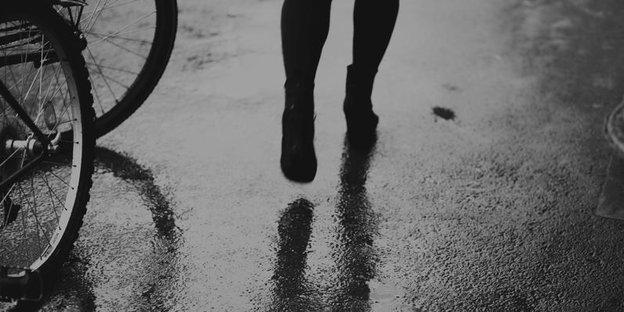 Ausschnitt des Schwarz-weiß-Bildes, der Füße und Waden einer Frau zeigt, die an Fahrradreifen vorbeiläuft