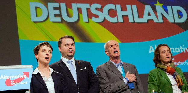 Vier Personen stehen auf einer Bühne vor der Projektion einer Deutschlandfahne. Ihre Münder sind geöffnet.
